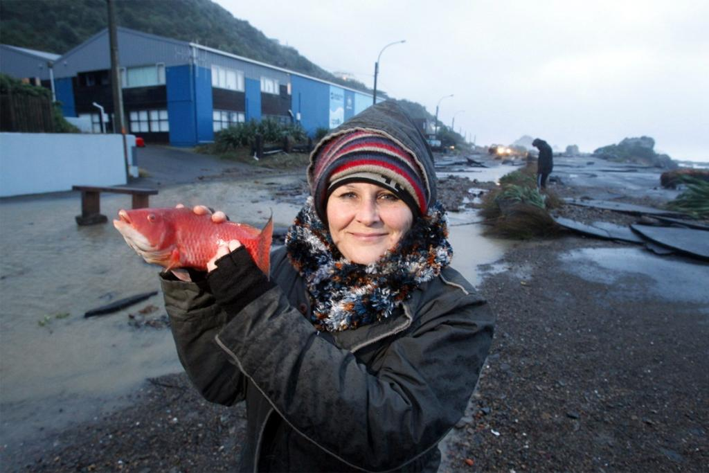 South coast resident Karen Brodie with a fish she found washed up on the Esplanade.