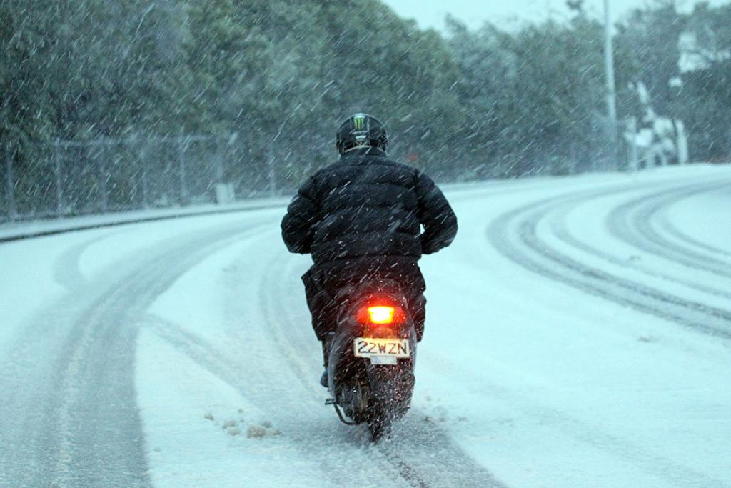 WINTER DRIVE: A scooter rider braves the snow in Hackthorne Rd, Cashmere.