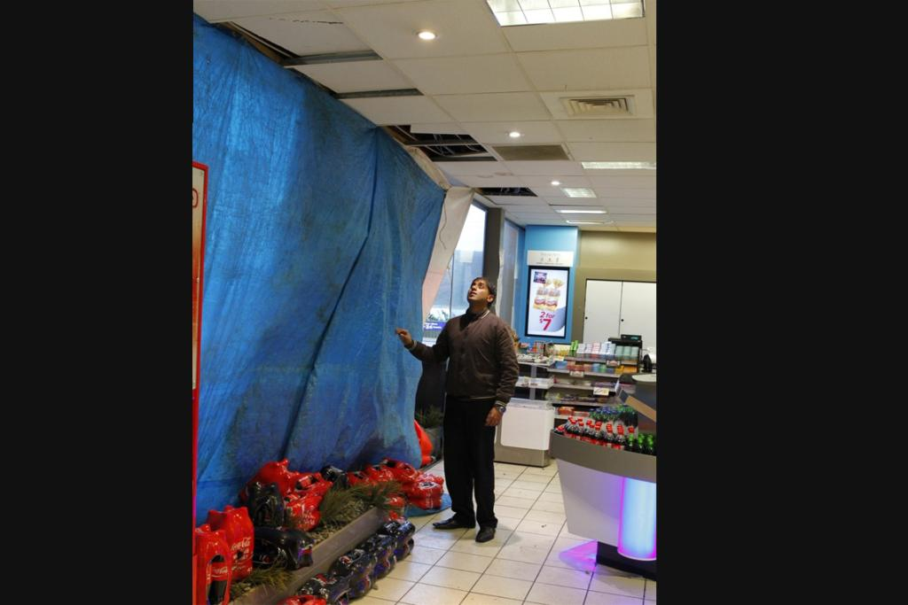 A Z Mana service station employee with his store's blown-in window this morning.