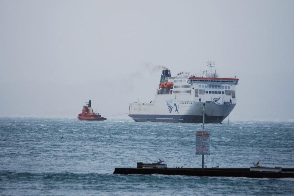 A tug boats attempts to tow the Interislander.