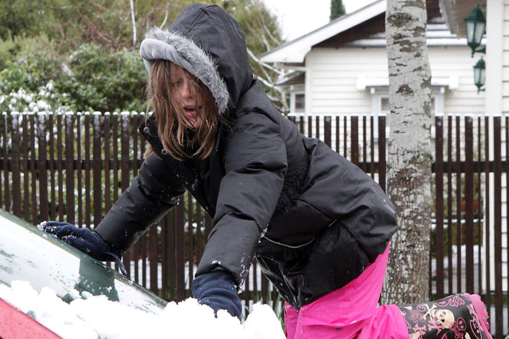 WILLING HELPER: Phoebe Sage, 8, of St Martins helps clear the snow.