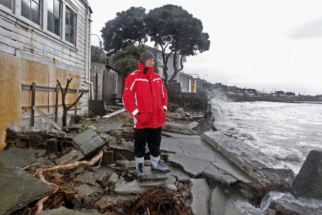 Reece Kohatu looks at the damage done by the waves at his Queens Drive Lyall Bay property.