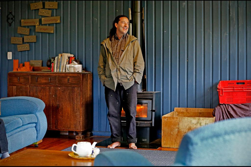 The 'barefoot bishop' stands in front of the fire.