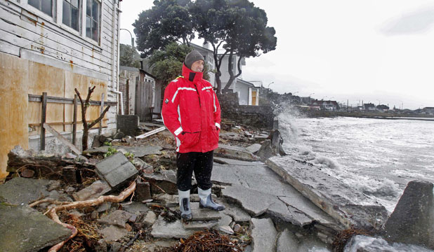 SURVEYING THE DAMAGE: Reece Kohatu looks at the remains of the seawall smashed by waves which flooded his home.