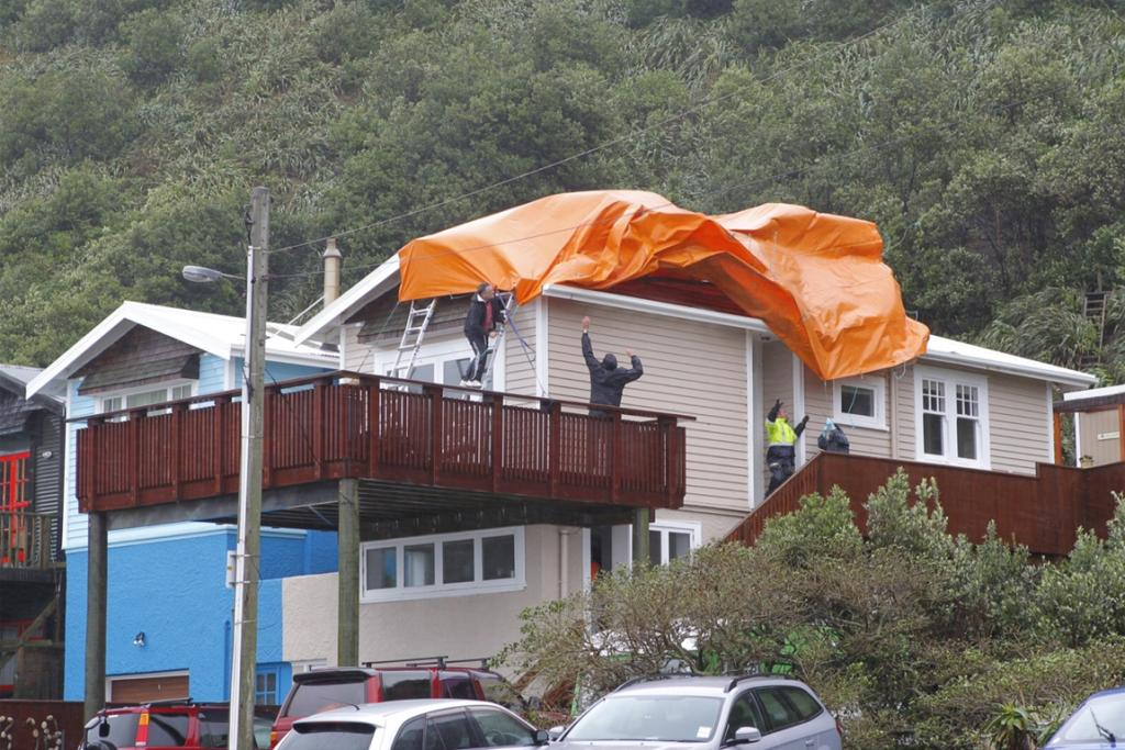 Residents putting a tarpaulin over a storm-damaged home at Queens Drive, Lyall Bay.