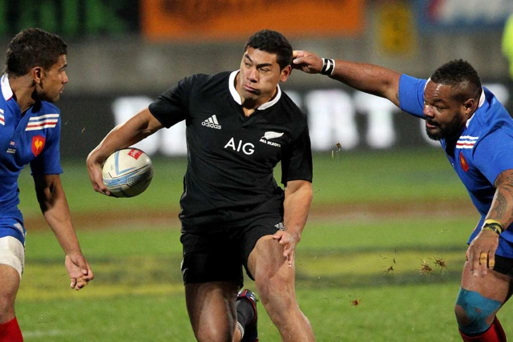 Charles Piutau charges into two French players.