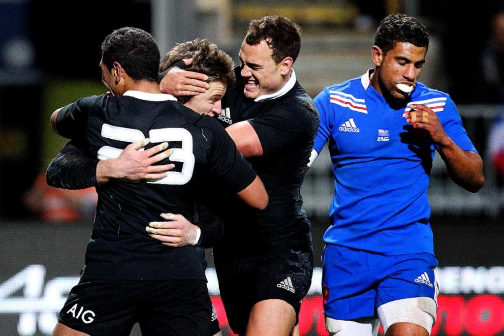 Beauden Barrett is mobbed by Charles Piutau and Israel Dagg after his late try.