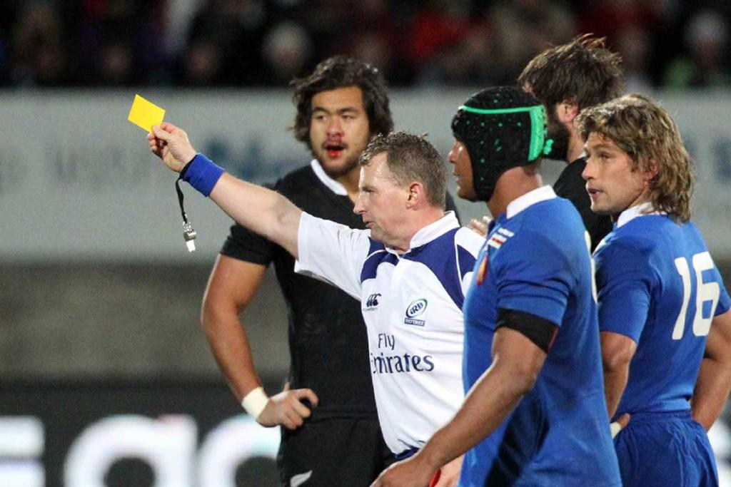 Referee Nigel Owens shows a yellow card to a French player.