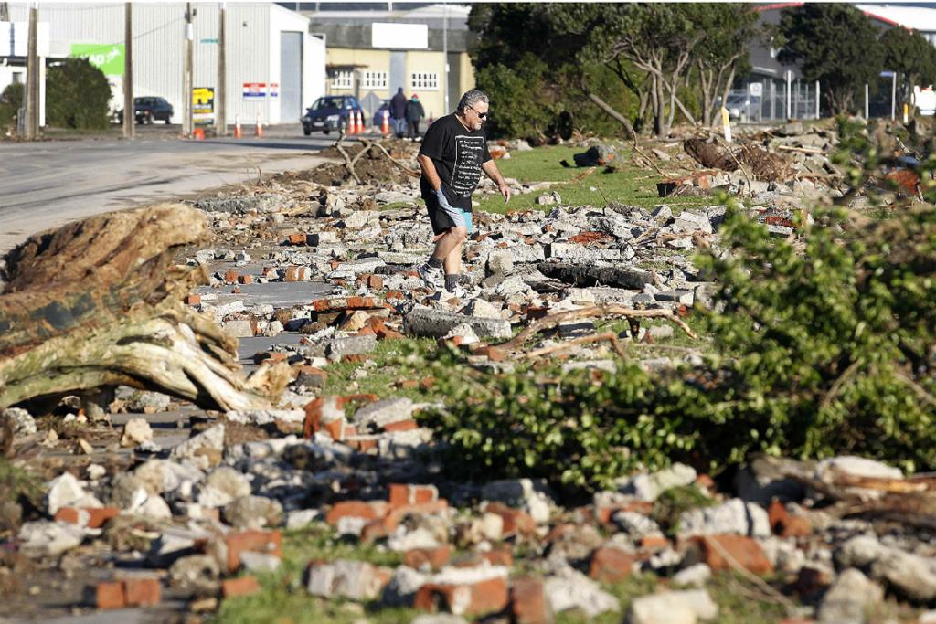 A man picks his way through debris washed up along Port Rd in Seaview.