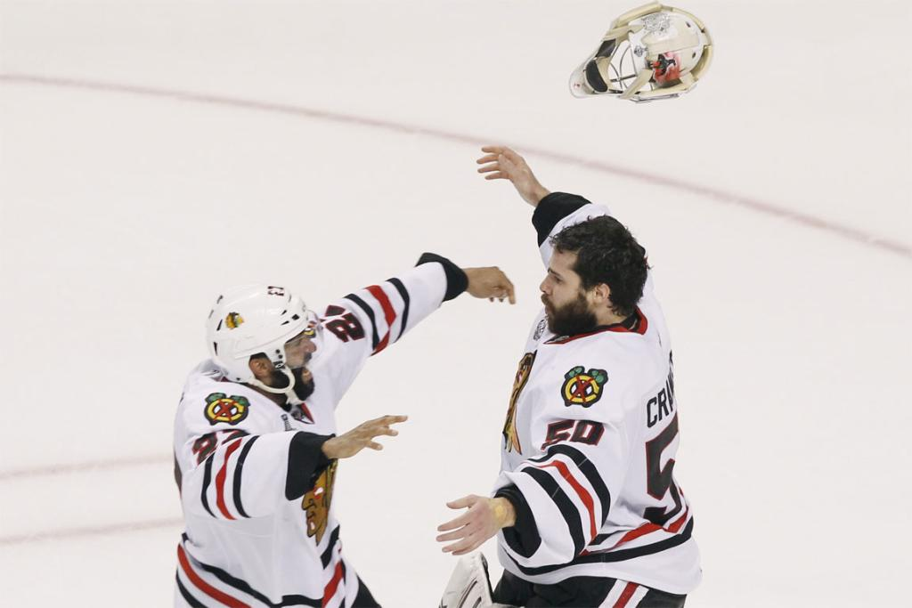 Chicago Blackhawks goalie Corey Crawford (right) and teammate Johnny Oduya celebrate their team's Stanley Cup triumph.