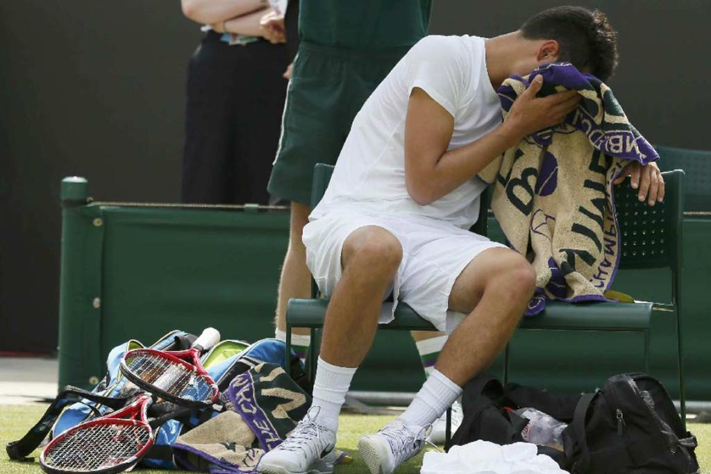 An ill Bernard Tomic covers his face with a towel during a change of ends.