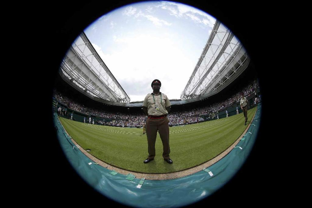 A soldier stands on Wimbledon's centre court during a break in play.