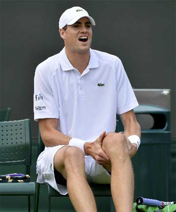 HURTING: John Isner flexes his left knee during a medical time out, before withdrawing from his second round match against Adrian Mannarino at Wimbledon.