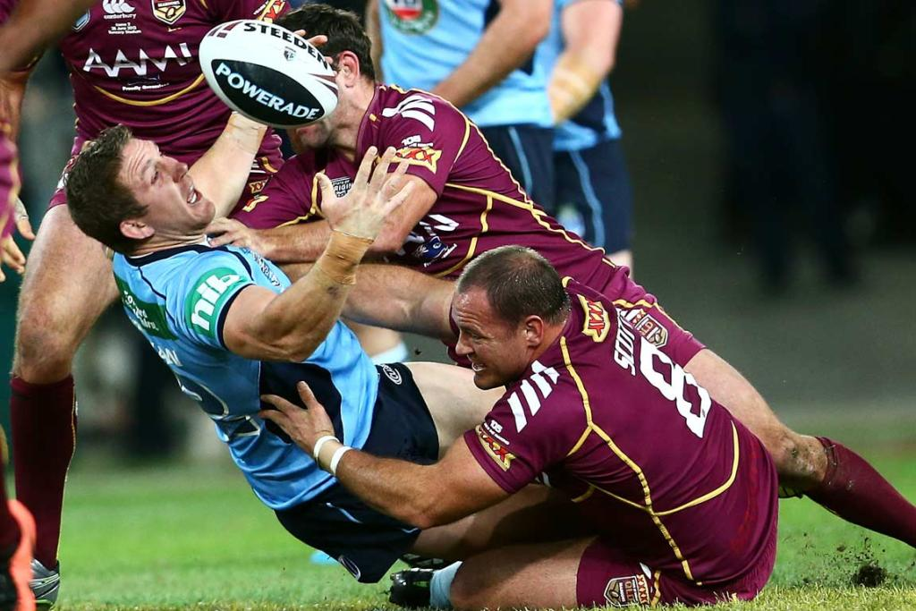 Ryan Hoffman loses the ball as he's tackled by Matthew Scott and Cameron Smith.
