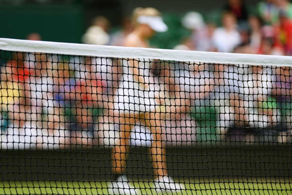 A player walks behind the net during a break at Wimbledon.