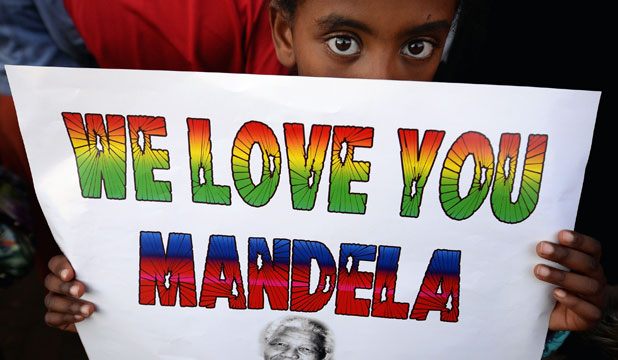 A child holds up a sign in support of former South African President Nelson Mandela outside the hospital in Pretoria where the anti-apartheid hero remains in a critical condition.