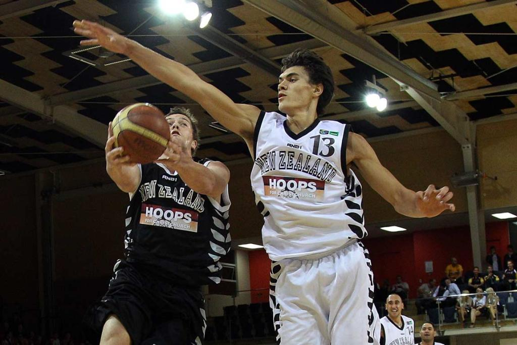 Wellington Phoenix footballer Danny Vukonic learns the hard way not to try to shoot on Steven Adams during a Christchurch Earthquake fundraising game.