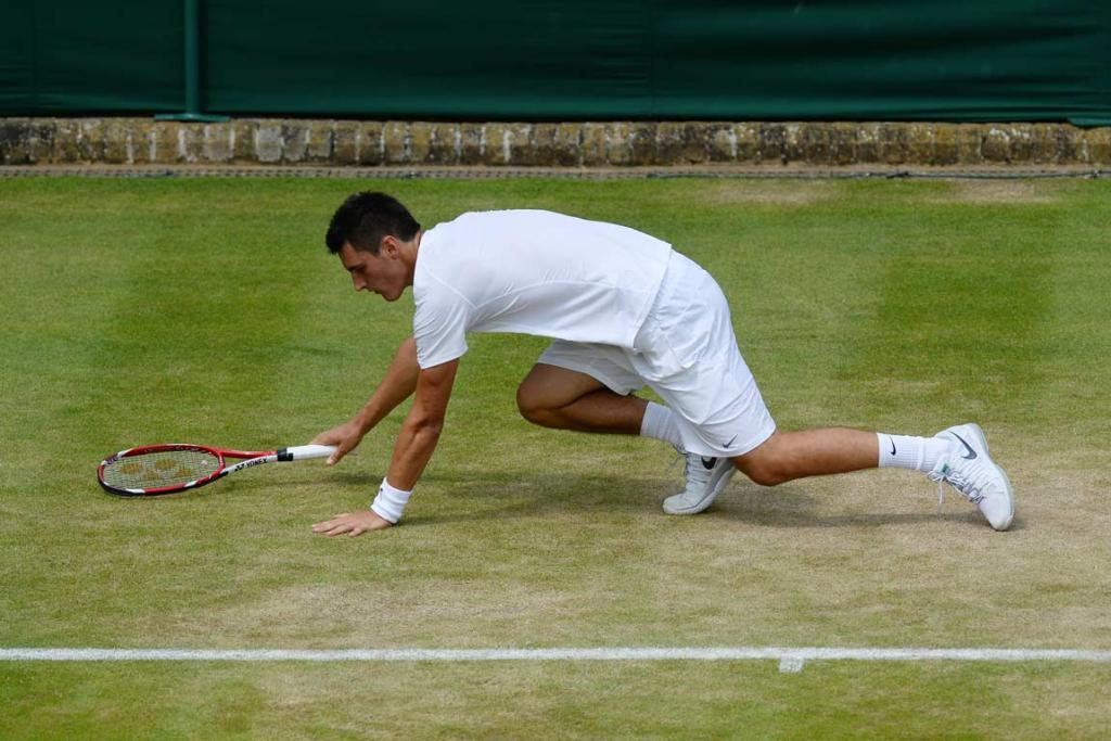 Bernard Tomic stumbles to the grass during his match against James Blake.