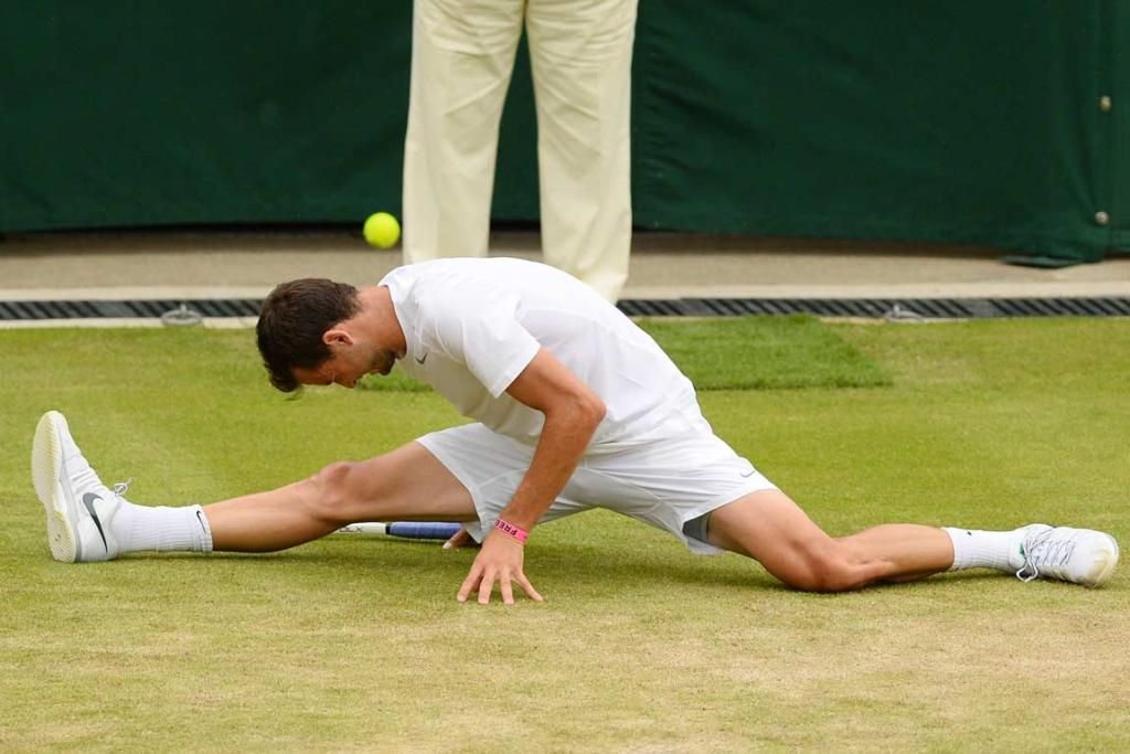 Bulgaria's Grigor Dimitrov slips into the splits on a slippery court against Grega Zmelja.