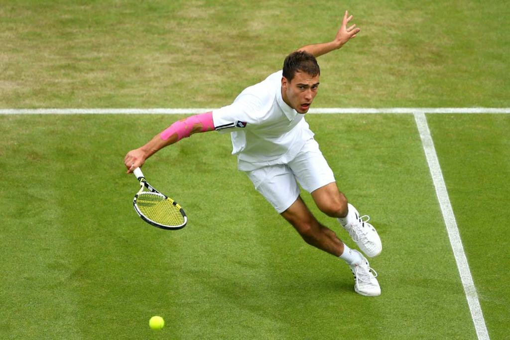 Jerzy Janowicz gets down low to play a backhand volley.