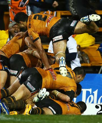 MAN-STACK: Wing David Nofoaluma dives onto the pile of Wests Tigers players celebrating Benji Marshall's try.