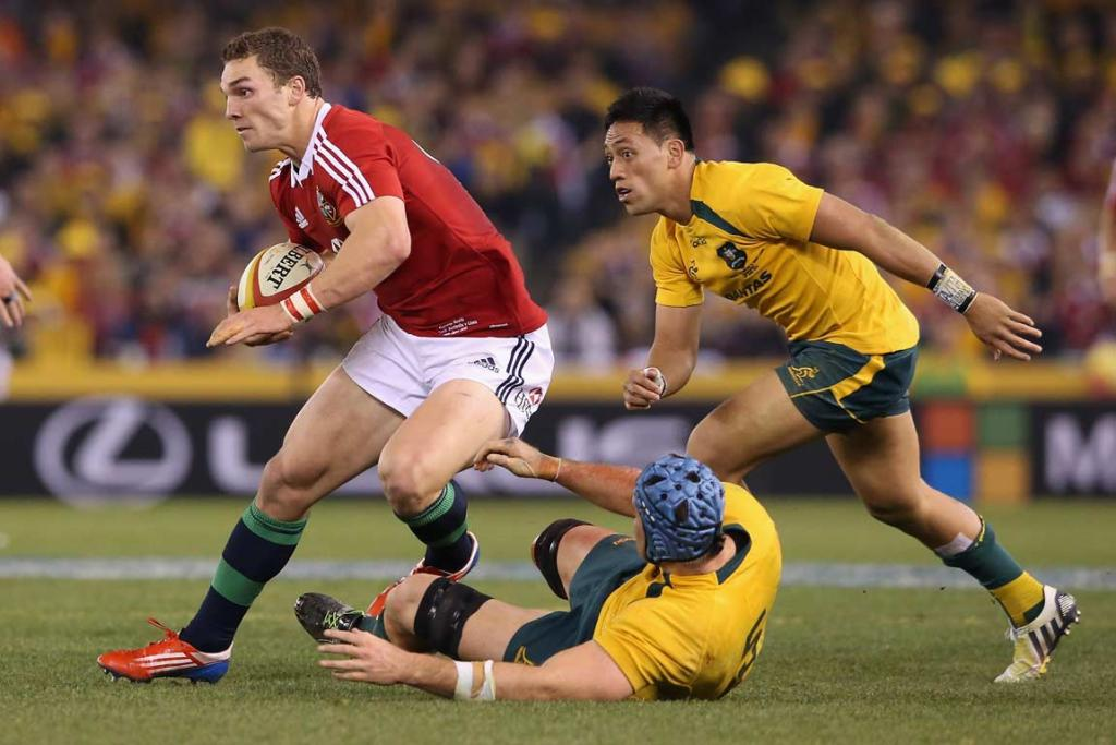 Lions wing George North evades two Wallabies players.