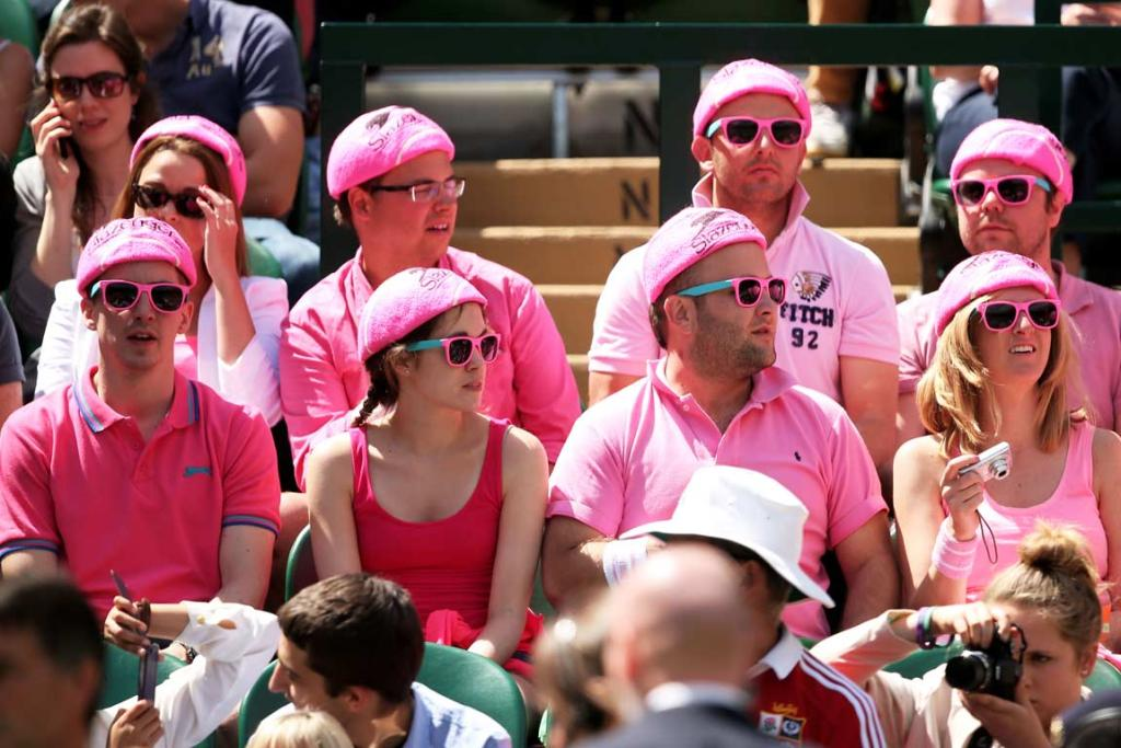 Wimbledon fans dressed in all in pink watch Bernard Tomic and Richard Gasquet.