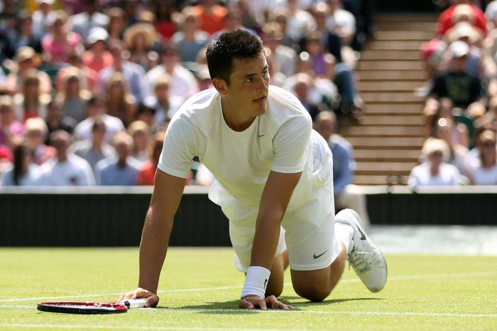 Bernard Tomic drops to all fours after hitting a shot at the net.