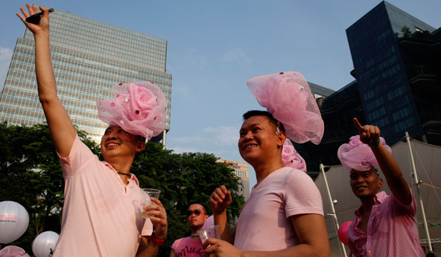 Participants dressed in pink enjoy a picnic before taking part in the forming of a giant pink dot at the Speakers' Corner in Hong Lim Park in Singapore.