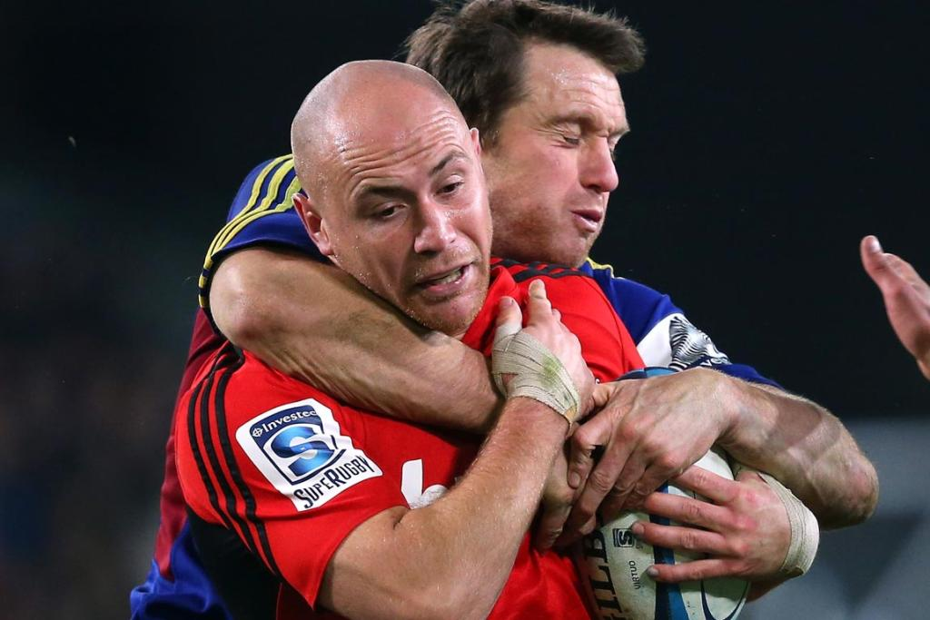 Willi Heinz of the Crusaders is tackled by Ben Smith of the Highlanders during the round 18 Super Rugby match between the Highlanders and the Crusaders.