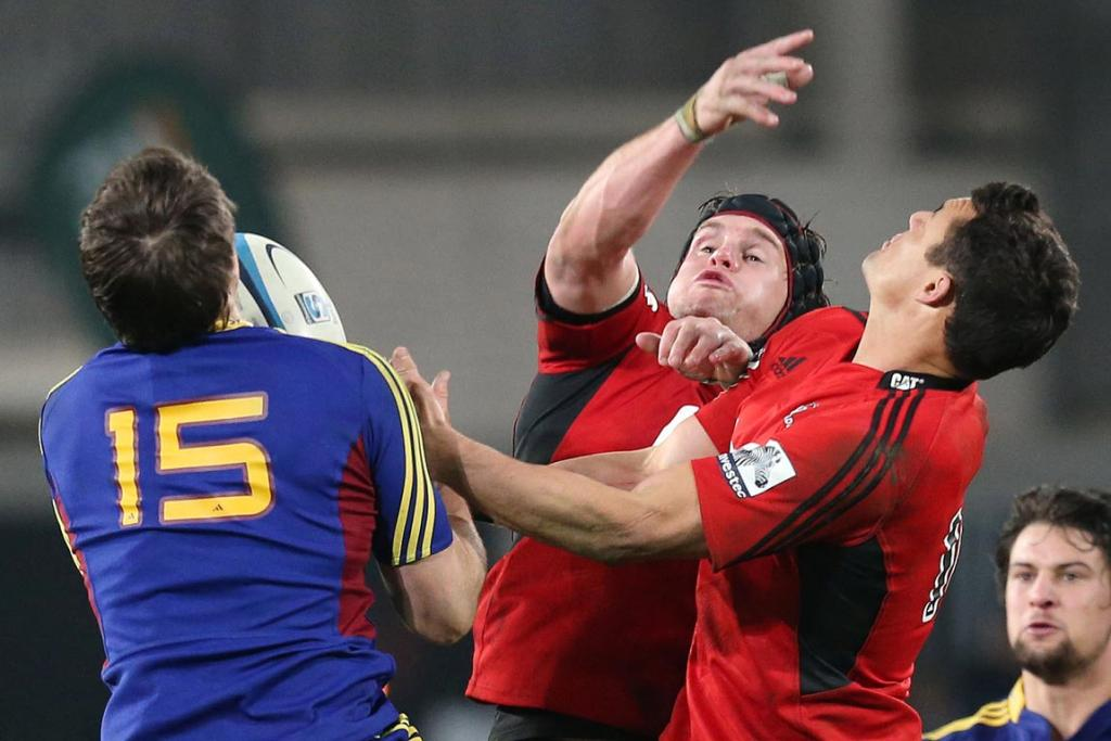Highlanders player Ben Smith jumping in the air for the ball with Crusaders Matt Todd & Dan Carter.