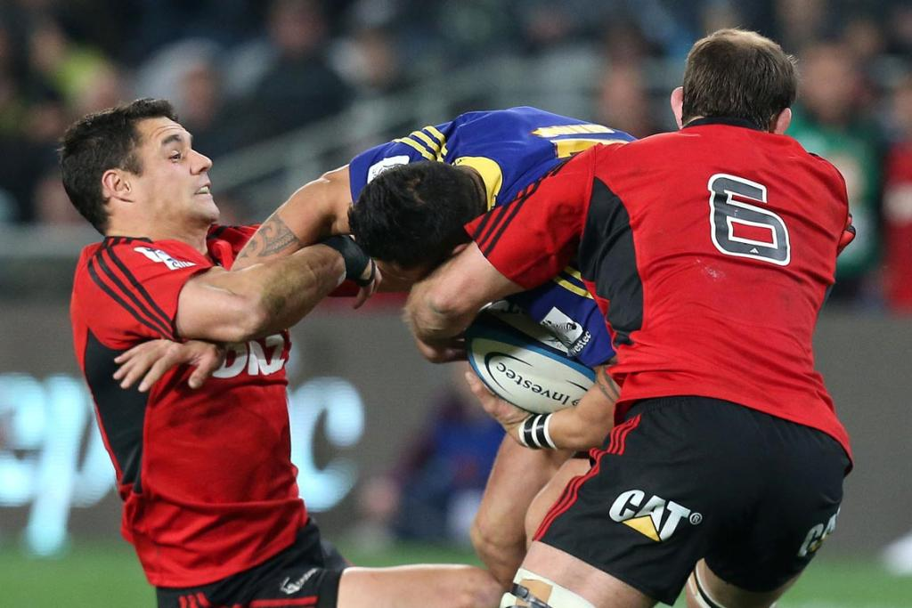 Highlanders player Hosea Gear being tackled by Crusaders players Dan Carter (left) & George Whitelock.