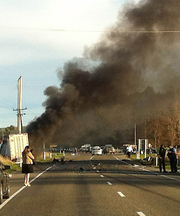 CRASH AFTERMATH: Smoke billows from a burning truck and trailer unit that came to rest against a power pole after a crash on State Highway 1 at Otaio.
