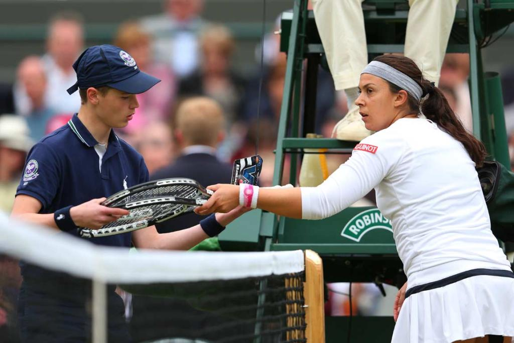 Marion Bartoli is handed new racquets by a ball-boy during her match against Sloane Stephens.