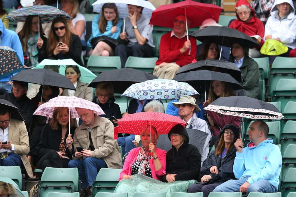Spectators huddle under umbrellas during a rain break at Wimbledon.