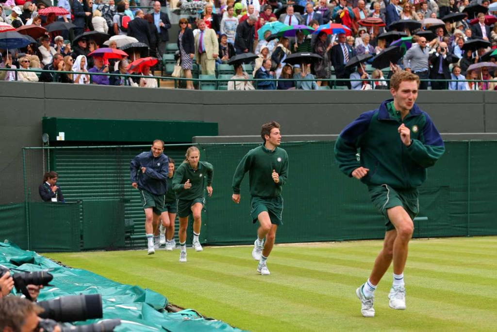 Wimbledon ground crew sprint out on the court to bring out the rain covers.