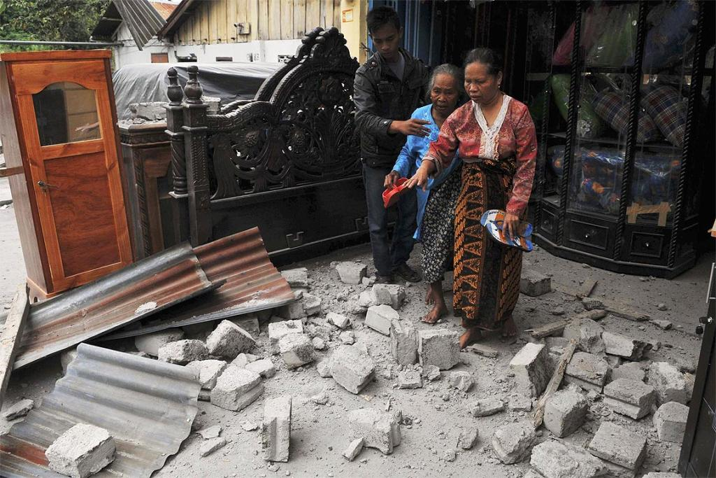 Residents leave their damaged house after it was hit by the strong earthquake in Bener Meriah district in Central Aceh.