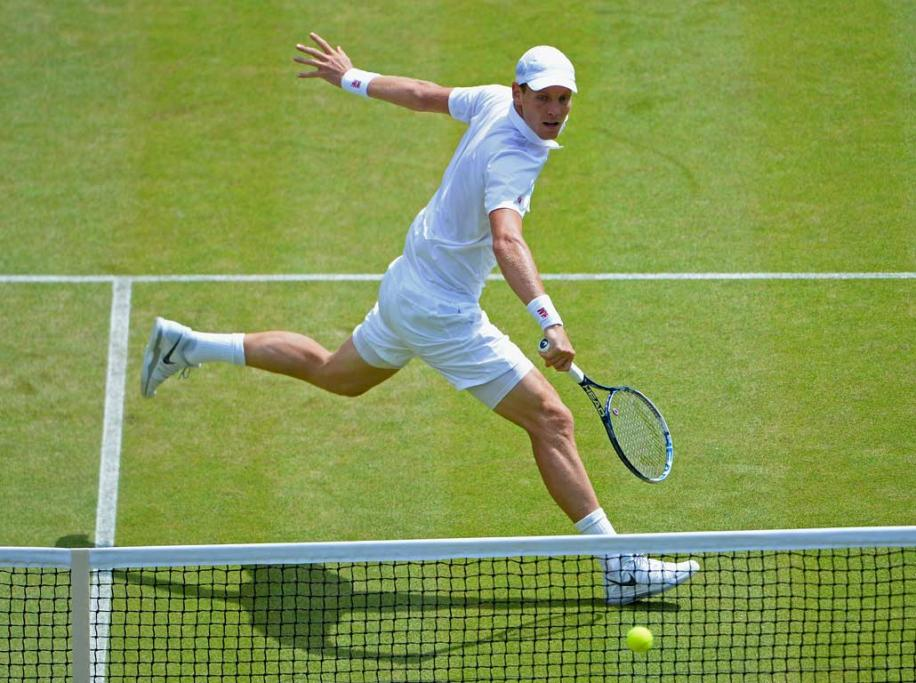 Tomas Berdych squeezes a backhand volley over the net.