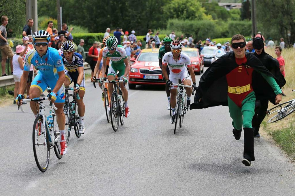Tour de France spectators, dressed as superheroes Batman and Robin, run alongside riders.