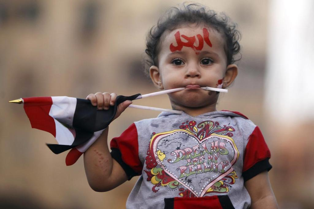 "A girl with the colours of the Egyptian flag and the word ""leave"" painted on her face in Tahrir Square."
