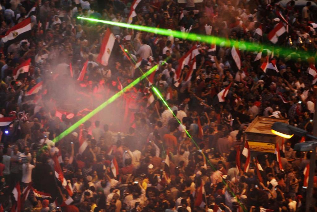 Laser lights are flashed as protesters against Egyptian President Mohamed Morsi gather in Tahrir Square in Cairo. Laser lights were used against helicopters.