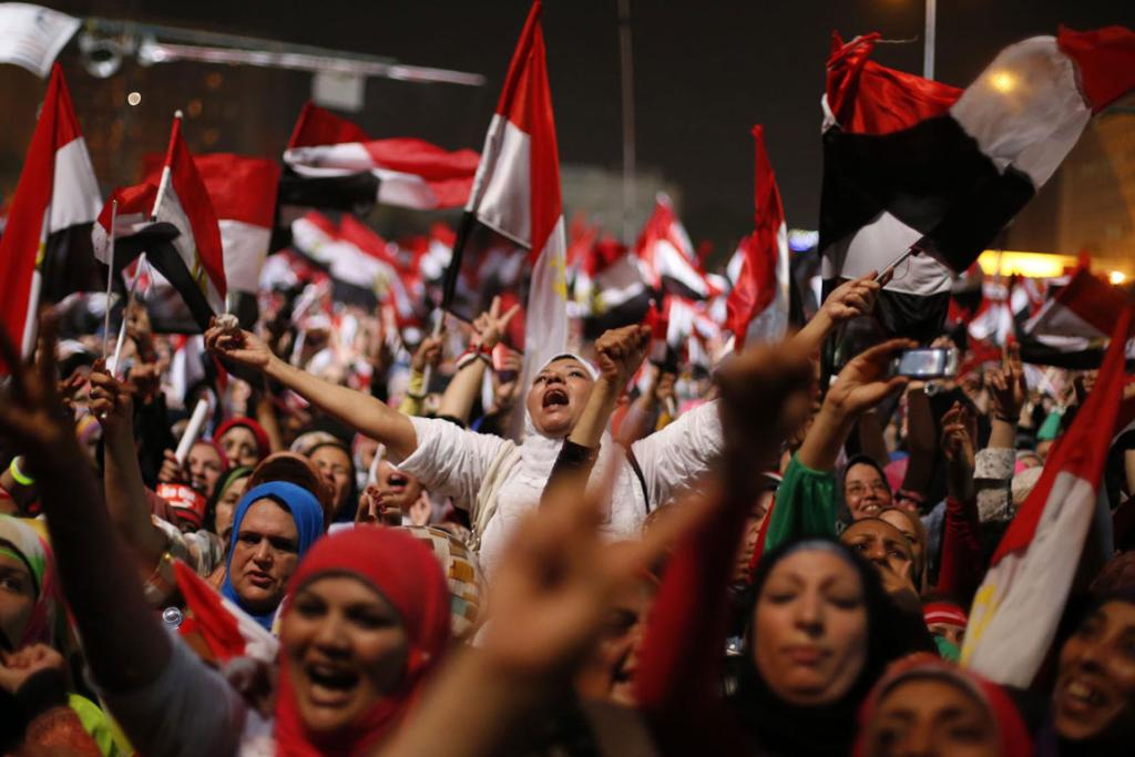 Protesters against Egyptian President Mohamed Morsi wave national flags in Tahrir Square in Cairo.