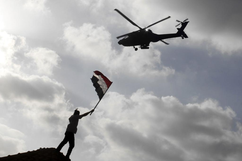 A supporter of President Mohamed Mursi waves with his flag to a military helicopter passing over during a protest to counter anti-Mursi protests elsewhere in Alexandria.