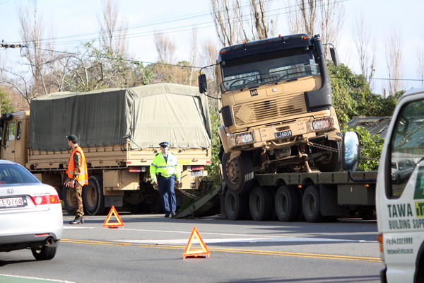OOPS: The army truck hangs off the side of a trailer which it was being loaded onto after breaking down.