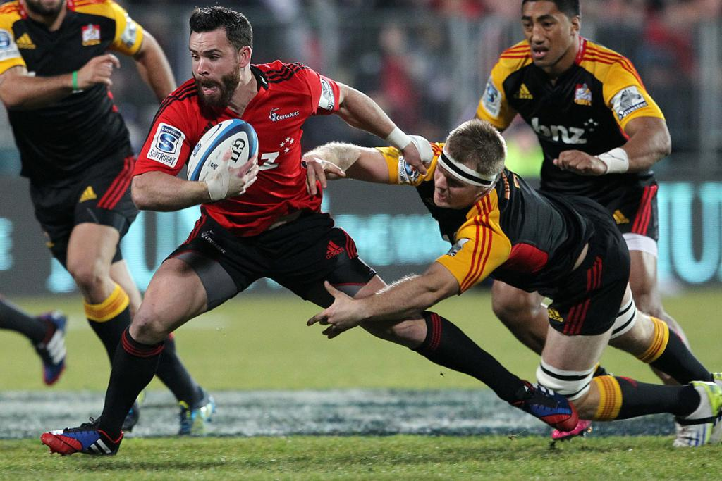 Crusaders centre Ryan Crotty tries to escape Chiefs flanker Sam Cane.