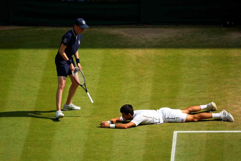 Novak Djokovic is handed his racquet by a ballboy after falling while diving to play a shot.