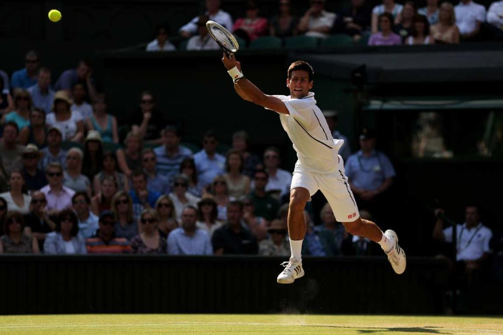 Novak Djokovic leaps in the air as he returns a Juan Martin del Potro serve.