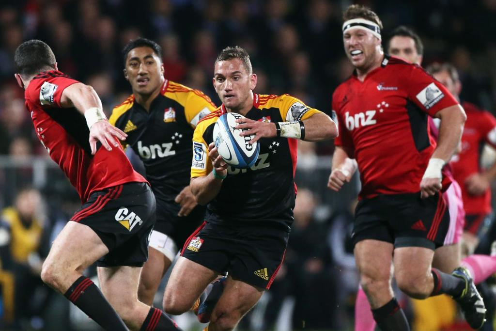 Aaron Cruden of the Chiefs runs with the ball into defender Tom Marshall of the Crusaders during the round 19 Super Rugby match between the Crusaders and the Chiefs.