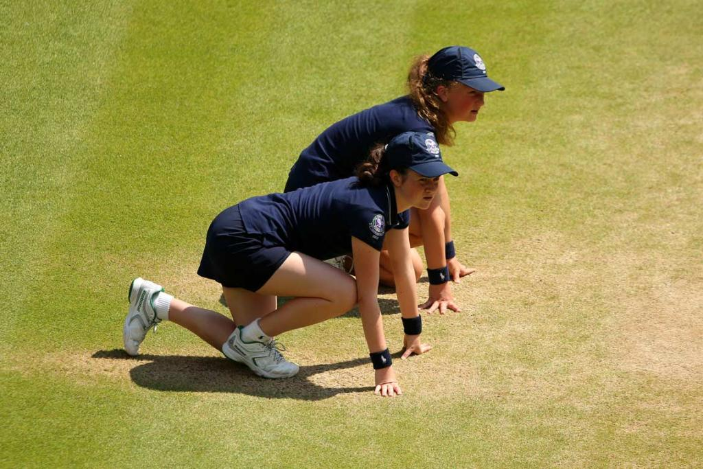 Wimbledon ballgirls wait while a point is played.