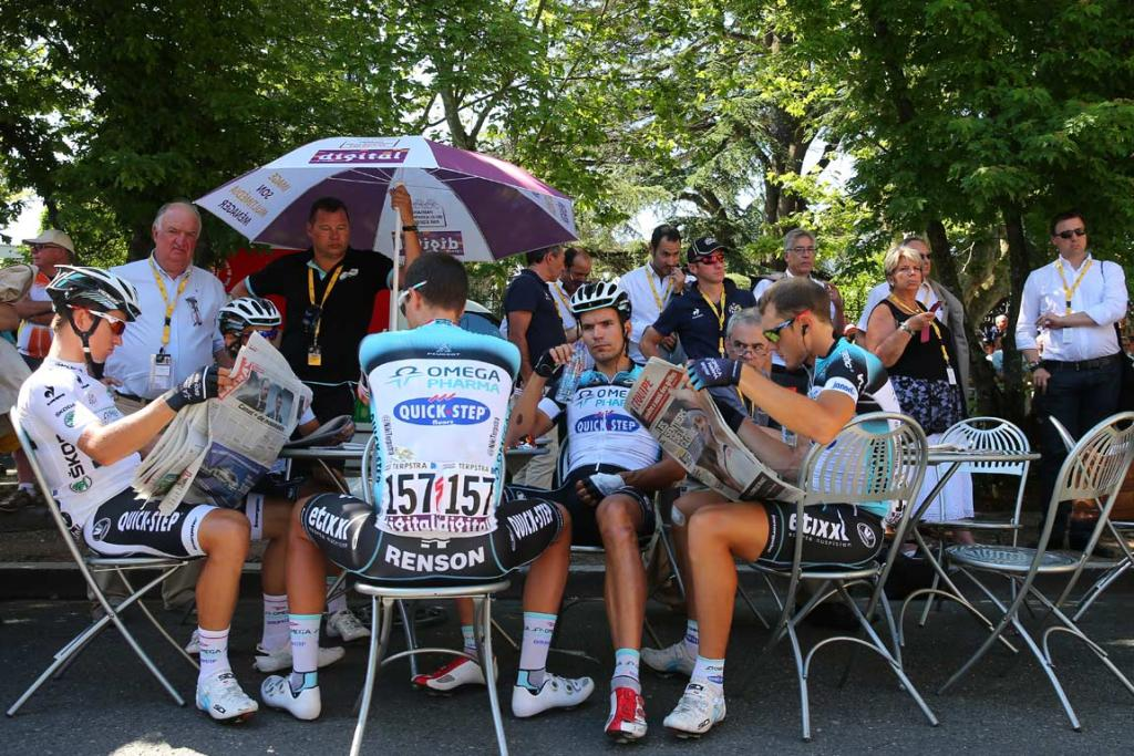 Team Omega Pharma-Quick Step readers read newspapers before the start of the stage.